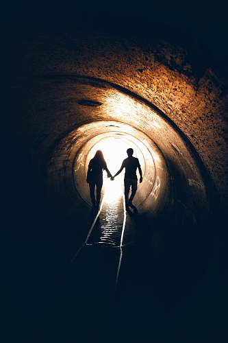 human silhouette of man and woman inside tunnel tunnel