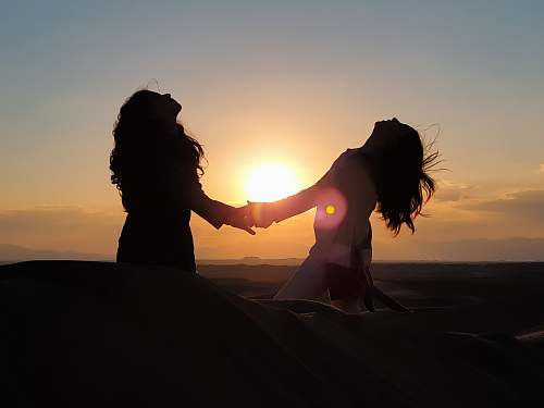 nature silhouette photo of two women holding each other hands outdoors