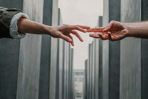 human two person touching each others finger tips hand