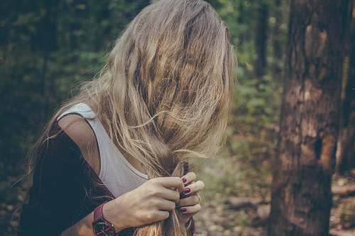 people woman holding her hair in forest woman