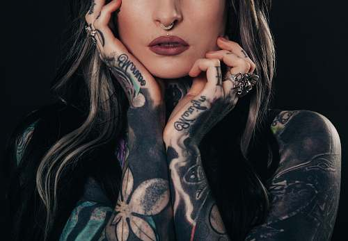 people woman showing body tattoo while holding her face tattoo