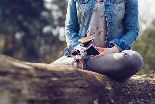 human woman sitting on log holding camera and book people