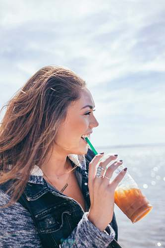people woman wearing black and grey jacket holding glass cup while drinking near body of water during daytime smiling