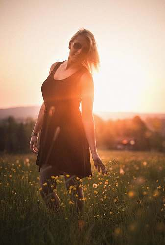 people woman wearing black scoop-neck mini dress surrounded by flowers during sunset woman