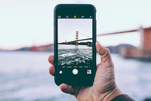 photo fort point person taking photo of Golden Gate Bridge, California iphone free for commercial use images