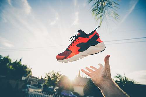 person unpaired orange and white Nike Air Huarache sunset