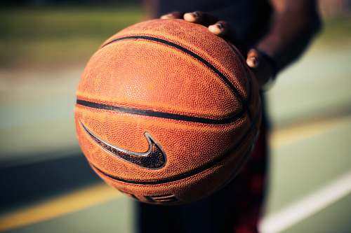 basketball person holding brown Nike basketball nike