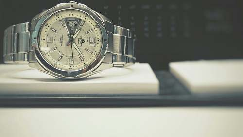 hand round silver-colored bezel analog watch with link bracelet on white board face