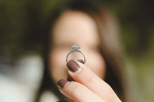 hand shallow focus photography of woman holding a diamond ring ring