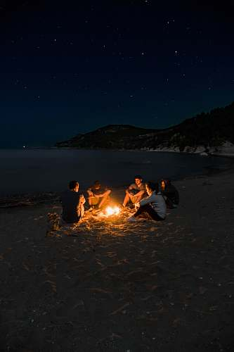 flame people sitting near campfire near seashore camping