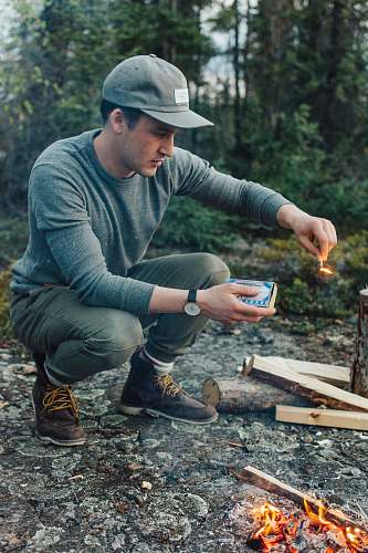 human selective focus photography of man holding lit matchstick outdoors people
