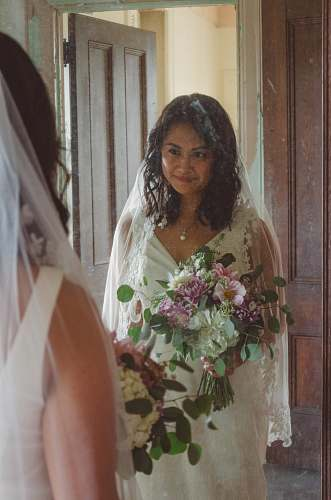 clothing smiling woman in front of mirror wearing white wedding gown and holding flowers human
