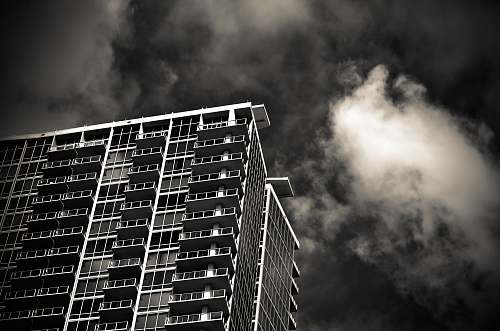 building grayscale photography of building under cloudy sky urban