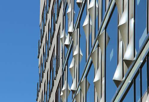 building low-angle photography of curtain wall building under blue sky at daytime facade