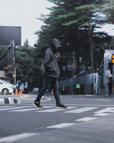 tarmac photography of man wearing black hooded jacket and blue denim jeans passing by the pedestrian lane road