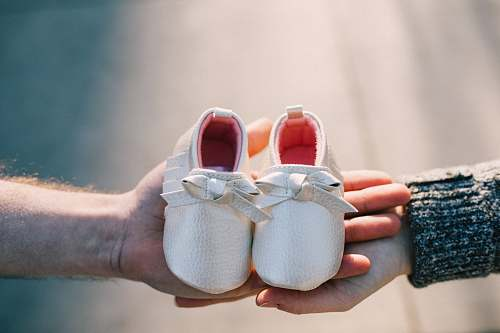 clothing two person holding pair of baby's shoes shoe