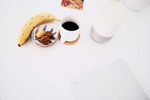 food white ceramic mug beside yellow banana flower fruit