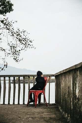 handrail boy sitting on armless chair beside baluster railing