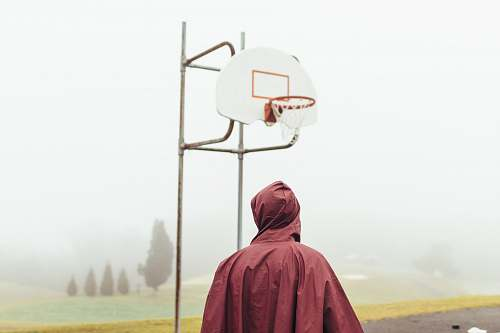 outdoors person wearing maroon raincoat standing under white and grey basketball hoop during foggy daytime outdoor