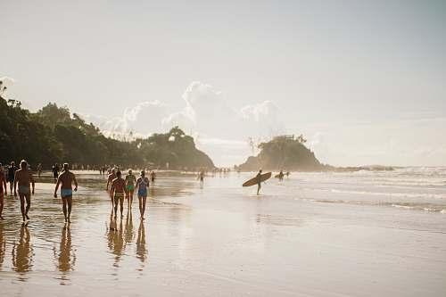 sea people walking along beach during daytime coast