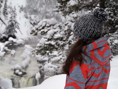 hat woman standing on snow field near trees winter