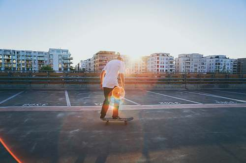 photo germany man riding skateboard on parking lot near buildings during golden hour skate free for commercial use images