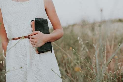 woman woman in white sleeveless dress holding book church