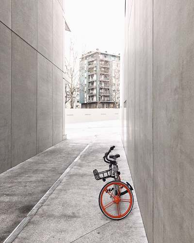 bike black and orange bicycle in between concrete walls italy