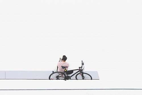 bike man sitting beside black mountain bike transportation