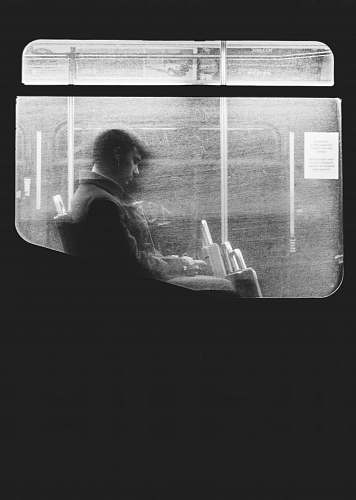grey Black and white shot of man sitting on night bus through dirty window in Boston window