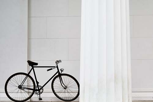 photo bicycle black bicycle standing on white concrete building bike free for commercial use images