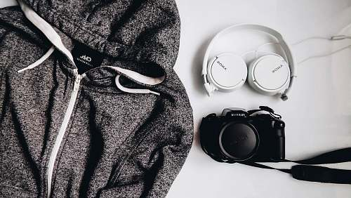 grey black DSLR camera and white Sony wireless headphones beside gray and white zip-up hooded jacket romania