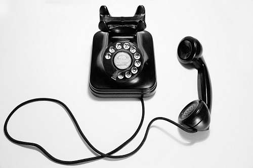 phone black rotary dial phone on white surface electronics