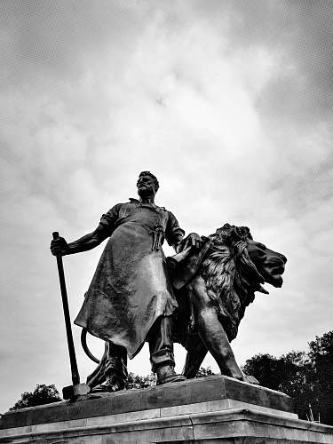 monument concrete man beside lion statue statue