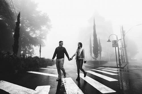 asphalt couple hold each other hands while walking on pedestrian lane tarmac