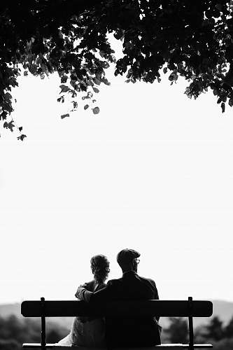 white couple sitting on bench under tree grayscale photography person