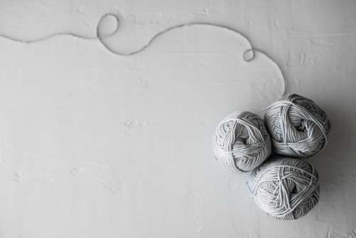 grey flat lay photography of three white yarn balls yarn