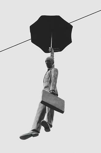 human floating man holding umbrella statue person