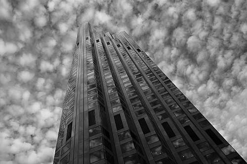 building grayscale low-angle photo of high-rise building under cloudy sky office building