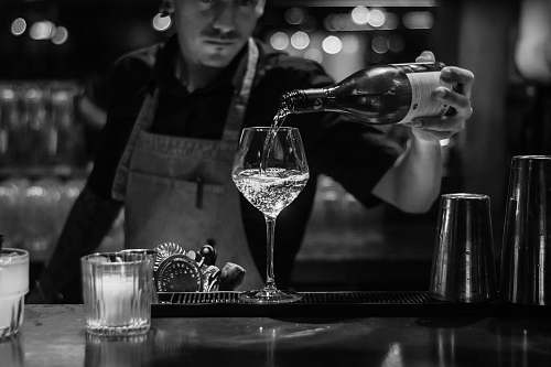 glass grayscale photo of bartender pouring liquid in wine glass human