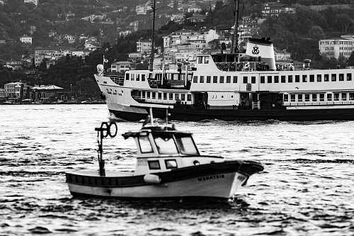 vehicle grayscale photo of boat and cruise ship on body of water person