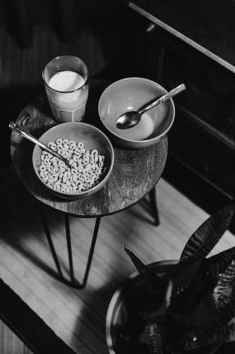 spoon grayscale photo of bowl of cereal beside glass of milk cutlery
