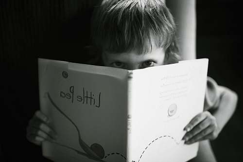 people grayscale photo of boy holding book reading