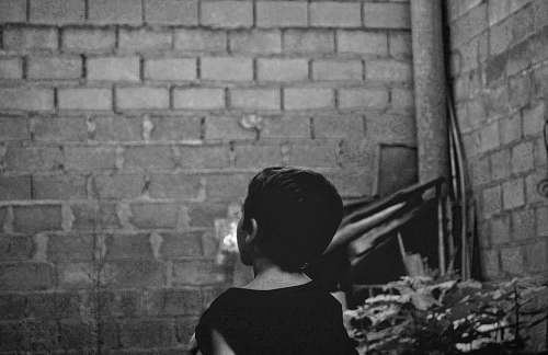 brick grayscale photo of boy standing near wall xàtiva