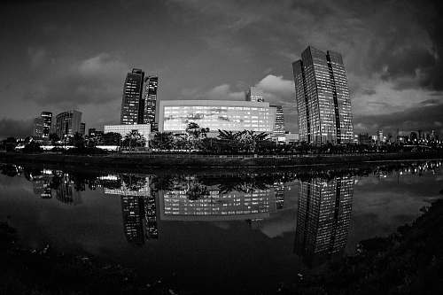 grey grayscale photo of buildings near body of water architecture