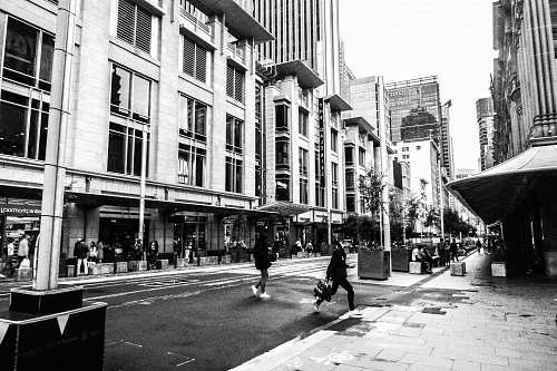 city grayscale photo of concrete buildings sidewalk