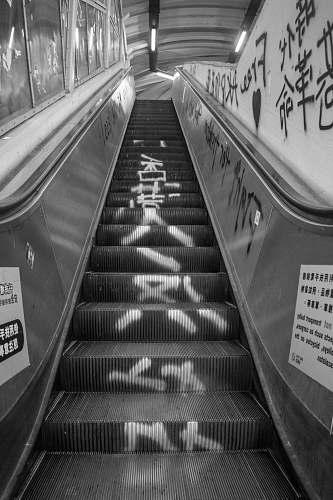 banister grayscale photo of escalator handrail