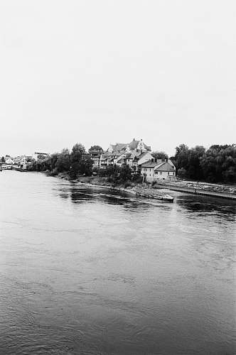 water grayscale photo of houses beside river nature