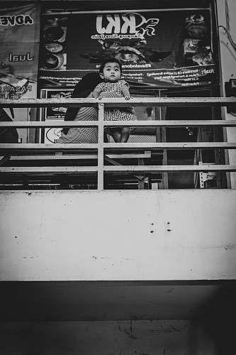surabaya grayscale photo of man holding baby while sitting on sofa indonesia