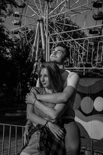 people grayscale photo of man hugging woman near Ferri's wheel human